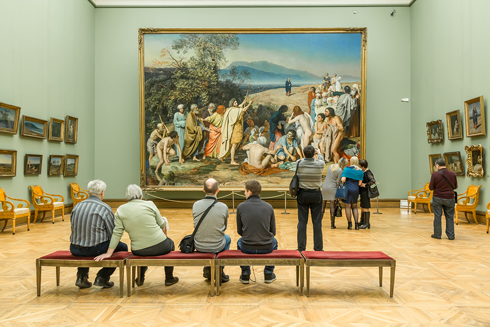 People sitting in front of a painting a museum