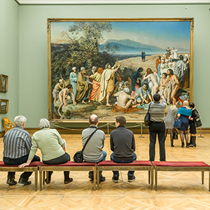 People sitting in front of a painting in a museum